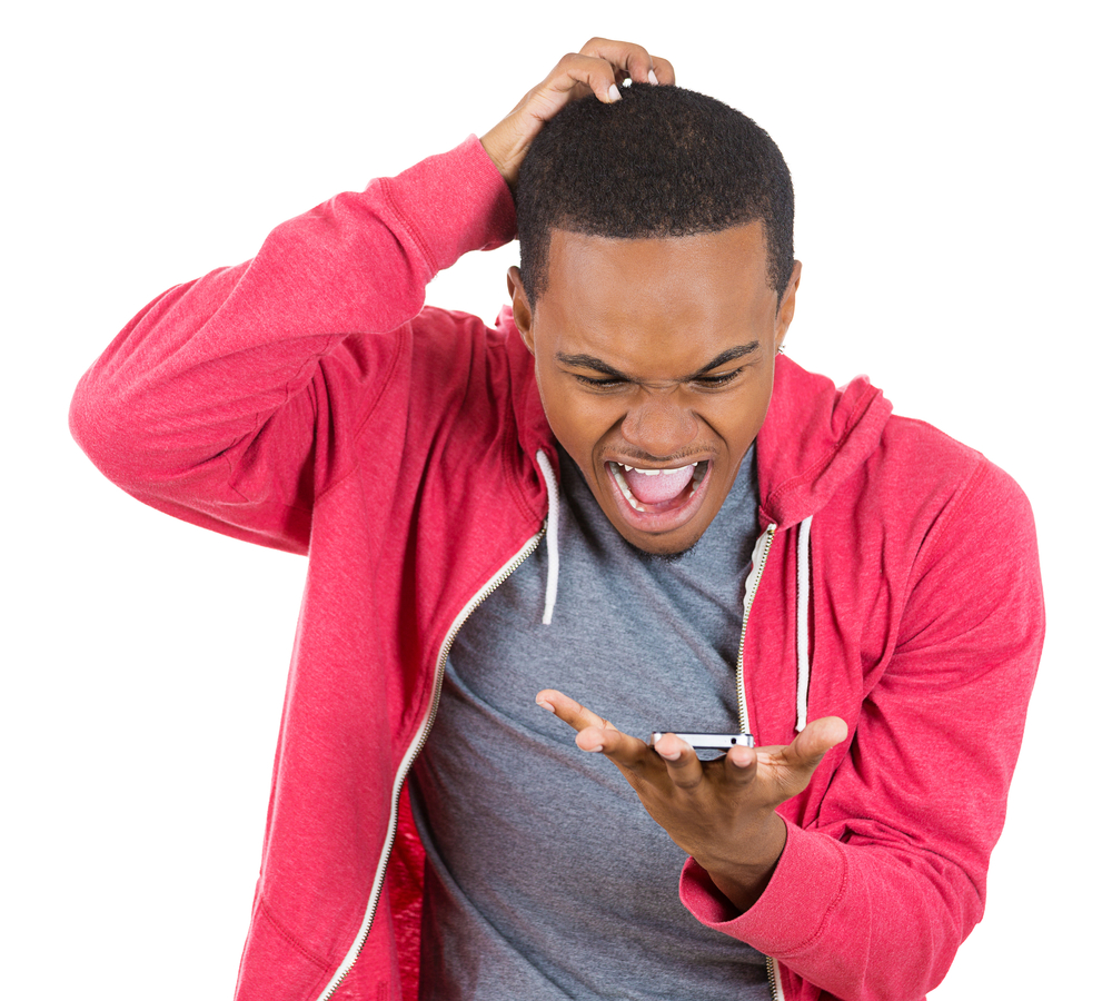 Closeup portrait of handsome young man shocked surprised, open mouth and eyes, mad by what he sees on his cell phone, isolated on white background. Negative human emotion facial expression feeling