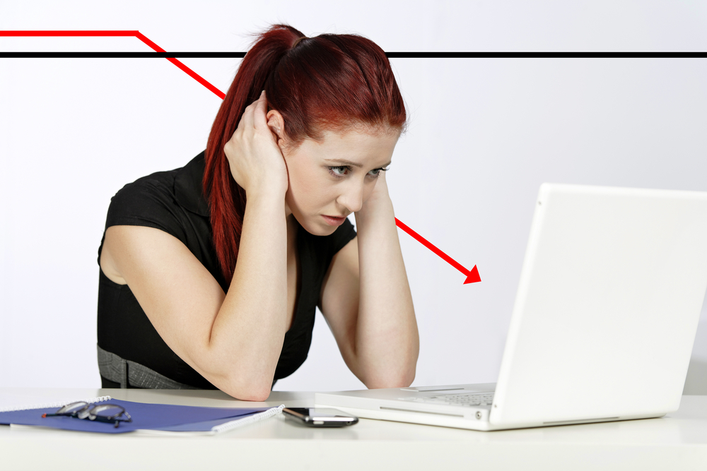 Professional woman showing concern at work using her laptop, displaying a concept graph in decline behind her