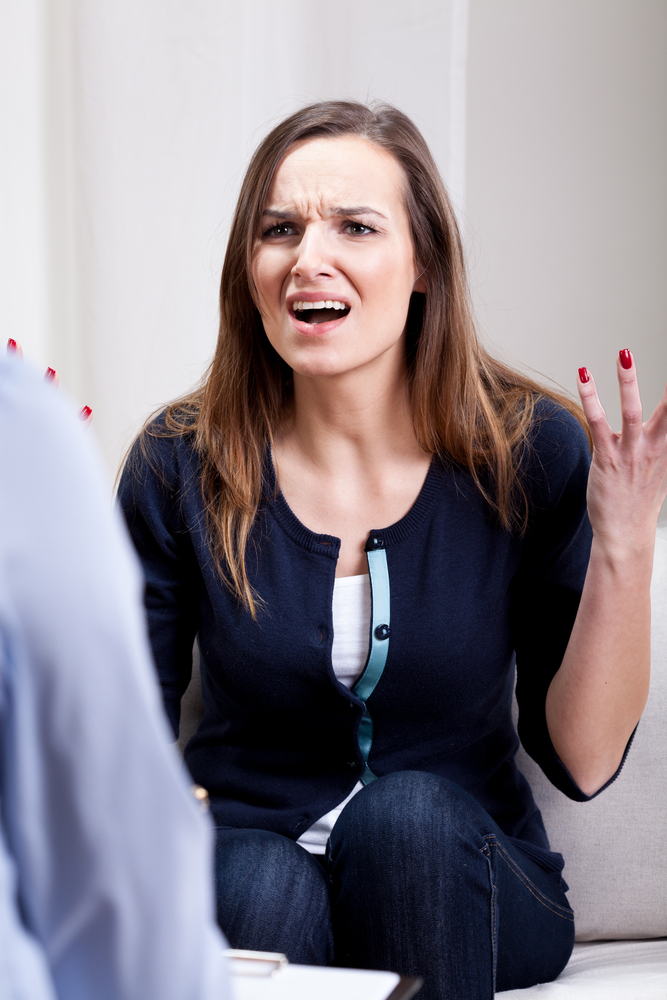 View of angry young woman during psychotherapy